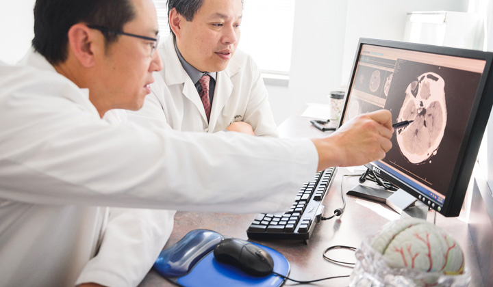 Dr. Jae Y. Lim discuss x-ray with colleague while pointing to a computer screen